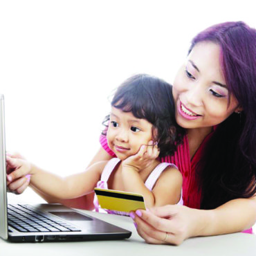 23669262 - young asian woman gives online shopping education to her daughter